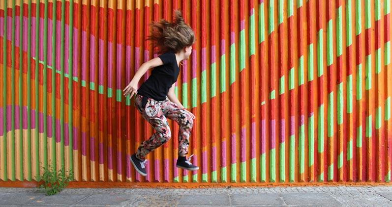 Mädchen vor einer bunten Wand springend